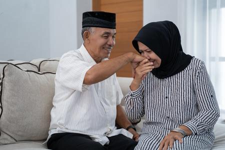 mature couple kissing husbands hand 版權商用圖片