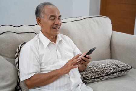 oude man die smartphone thuis gebruikt