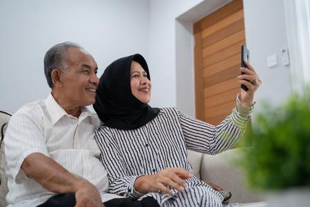 mature couple taking selfie using smartphone