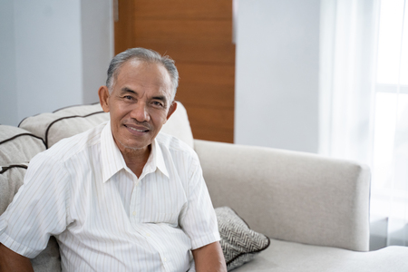 Asian old man sitting on the sofa with a smile looking at the camera Banque d'images