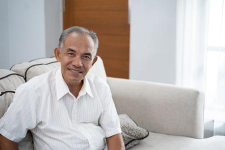 Asiatischer alter Mann, der mit einem Lächeln auf dem Sofa sitzt und in die Kamera schaut Standard-Bild
