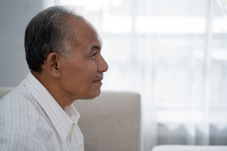 closeup from side view of Asian old man sitting on the sofa 免版税图像