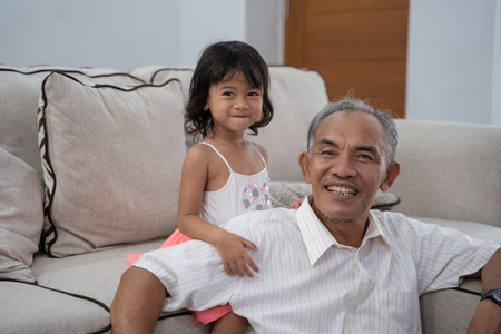grandfather and his granddaughter in livingroom at home 写真素材 - 117028182