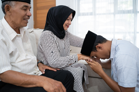 man kneeling and kiss his parents hand asking for forgivness