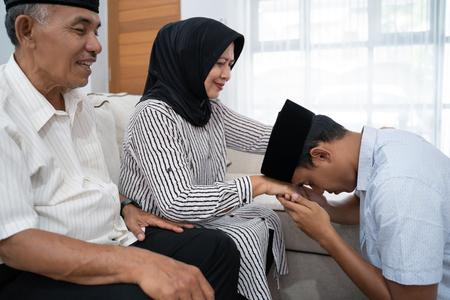 Mann kniet und küsst die Hand seiner Eltern und bittet um Vergebung Standard-Bild