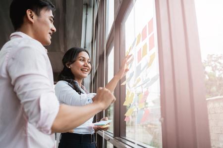 zakenpartner brainstormen door idee in het glazen raam te steken