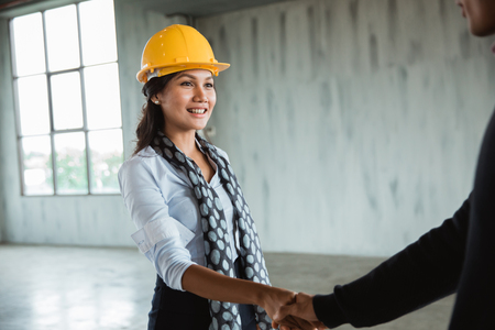 businesswoman with hardhat shaking hand Stock Photo