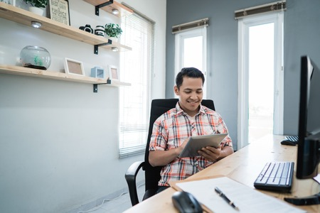 business owner relaxing using tablet at his office Imagens
