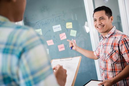 ein Arbeiter, der auf Papiernotizen an der Glaswand zeigt, um seinen Partner zu erklären