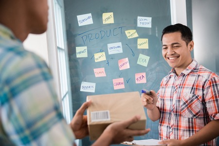 a man worker pointing to the box held by his partner for examples a good package with a address Imagens - 118386609