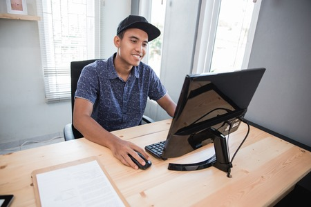 smiling young business man in his office Imagens