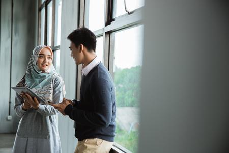 discussion entre collègues près des fenêtres avec tablette