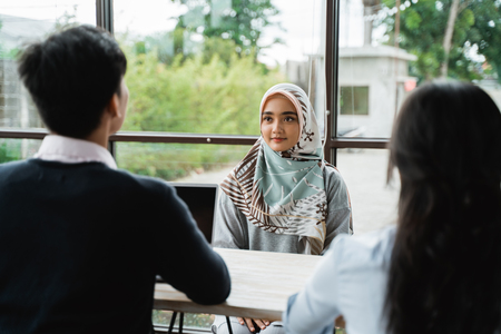 veiled women interviewed as new employees by two human resources departments