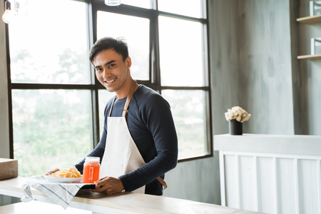 asian male waitress with food looking at camera and smiling