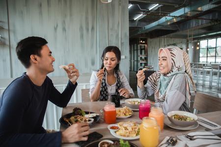 glückliche asiatische Freunde, die zusammen zu Mittag essen