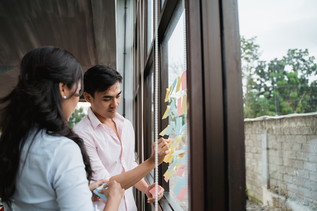 business partner brainstorming by sticking idea into the glass window