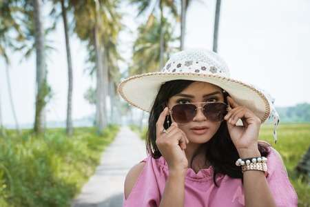 asian woman with sunglasses and hat
