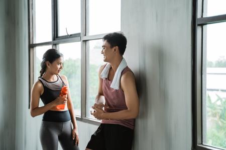 2つのスポーツカップルは、ワークアウト中に話を楽しむ