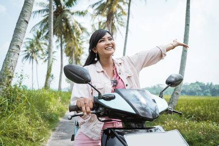 woman raised her arm while ride her scooter Stock Photo