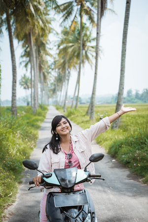asian woman enjoy riding her motorcycle in tropical country road