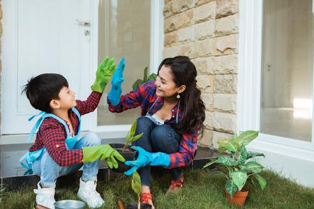 집에서 함께 정원을 가꾸는 동안 어머니와 아들 하이파이브
