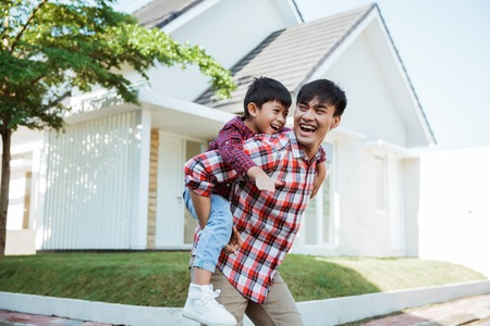 father piggyback ride with his son in front of the house