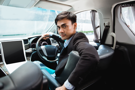 driver in his suit driving luxurious car