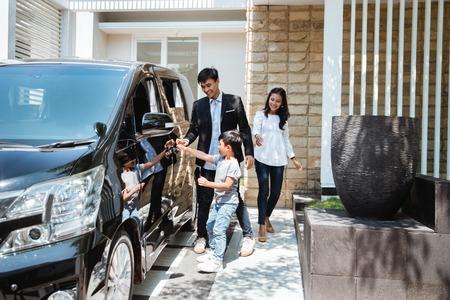 l'enfant essaie de monter dans la voiture avec ses parents