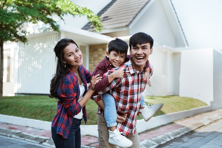 asian family standing in front of their new house together Banco de Imagens
