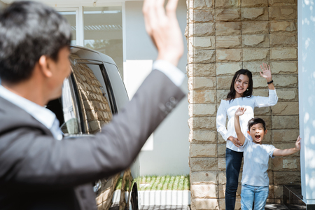 father waving goodbye to his family before going to work