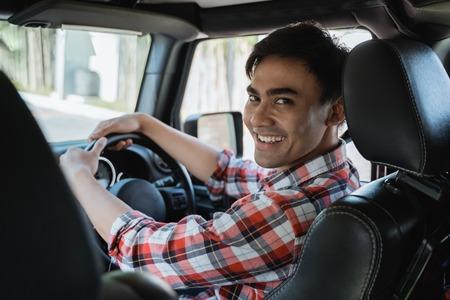 männlicher Fahrer, der nach hinten schaut