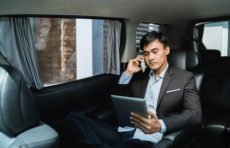 businessman calling by phone and using tablet  in the car Standard-Bild