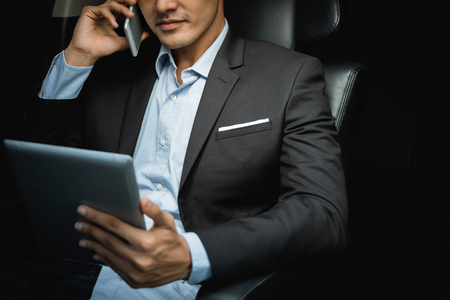 businessman calling by phone and using tablet in the car Stok Fotoğraf