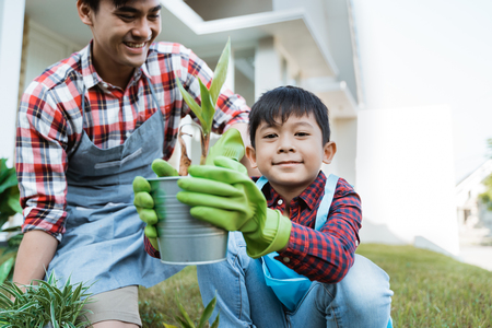 dad and son planting a plant gardening at their house together Banco de Imagens