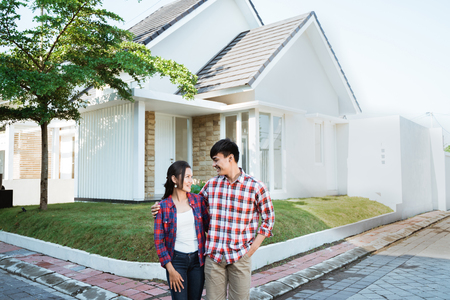 asian couple standing in front of their new house Standard-Bild