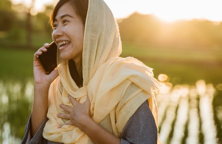 muslim happy asian woman talking on phone outdoor