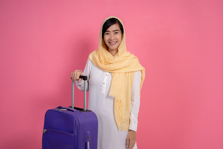 muslim woman with hijab holding suitcase