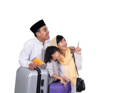 muslim family with suitcase looking up