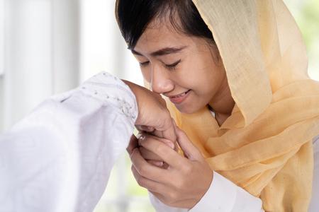 muslim woman with hijab kissing hand