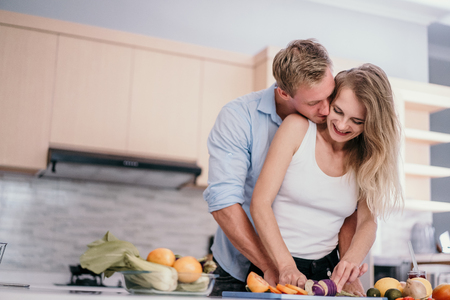 Romantic couple hugging and smiling while standing in the kitchen