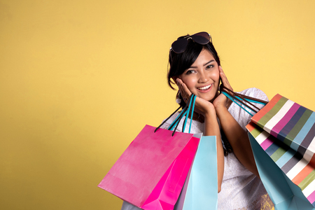 woman with shopping bags over Yellow background