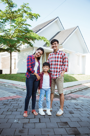 asian family standing in front of their new house together Reklamní fotografie