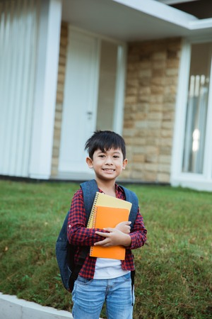 elementary student on the way to his school standing with backpack and book