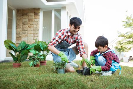 Vater und Sohn arbeiten morgens zu Hause im Garten
