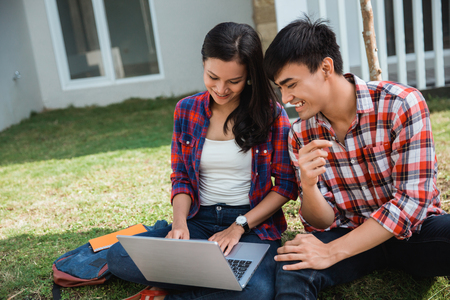 student friend in the park using laptop together Stock Photo - 121285982