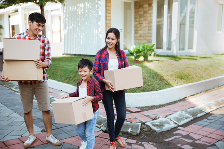 asian moving to new house carrying cardboard box Imagens