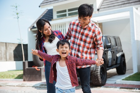 famille asiatique avec enfant devant leur maison et leur voiture