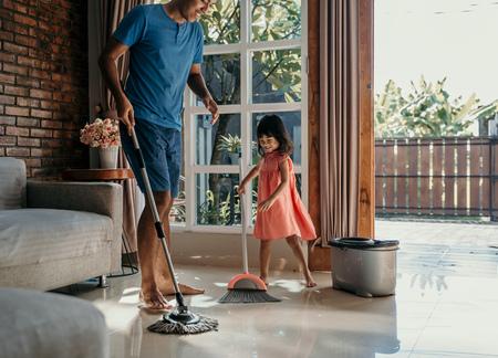 niña ayuda a su papá a hacer las tareas del hogar Foto de archivo