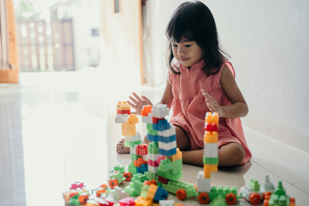 daughter playing with plastic brick at home
