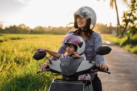 mamma e suo figlio si divertono a guidare lo scooter in moto Archivio Fotografico